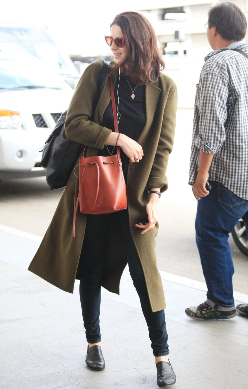Outlander actress Caitriona Balfe arrives in a olive green coat with red sunglasses with a red hand bag to match as she jets out of LAX Airport in Los Angeles, CA